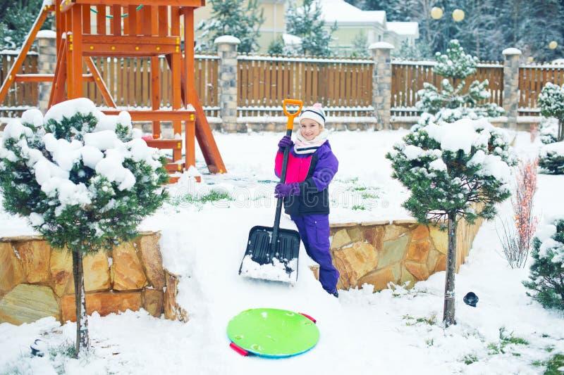 La fille heureuse active construit la glace et la colline de neige avec la pelle photo stock