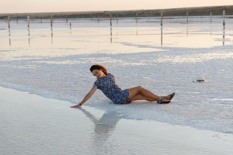 La fille heureuse appréciant le coucher du soleil, touche l'eau d'un lac de sel se reposant sur des cristaux images libres de droits