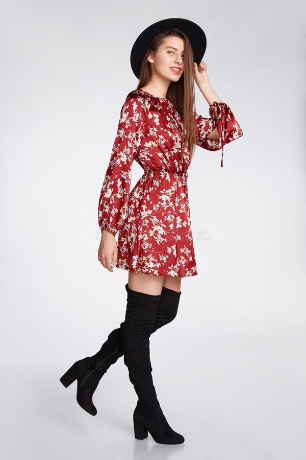 La fille heureuse attirante est possing et smilling dans la robe rouge de fleur et le chapeau noir sur le blanc photos libres de droits