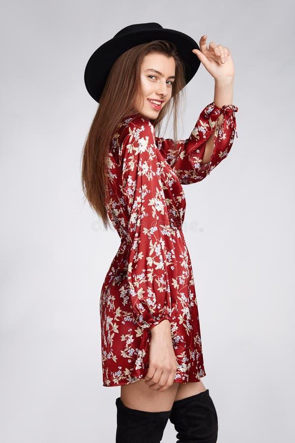 La fille heureuse attirante est possing et smilling dans la robe rouge de fleur et le chapeau noir sur le blanc photographie stock libre de droits