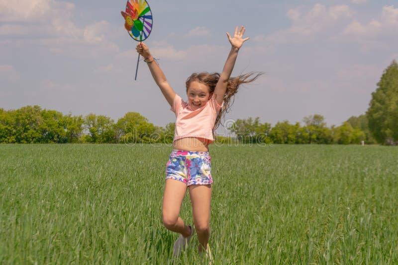 La fille heureuse avec de longs cheveux tenant un jouet coloré de moulin à vent dans des ses mains soulève sa main et sauts photographie stock