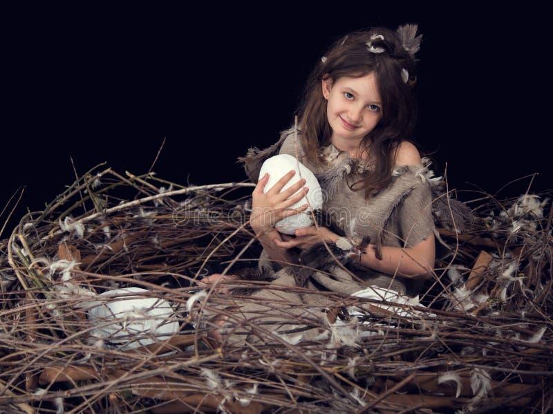 la fille heureuse avec des fleurs sur sa t?te s'assied dans un oeuf d?coratif avec le lapin de P?ques pelucheux mignon Oeuf de p? photo stock