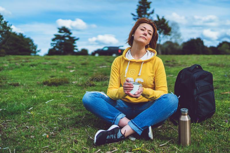 La fille heureuse avec des yeux a clôturé se tenir dans la tasse de mains de thé chaud sur l'herbe verte en parc naturel d'extéri images libres de droits