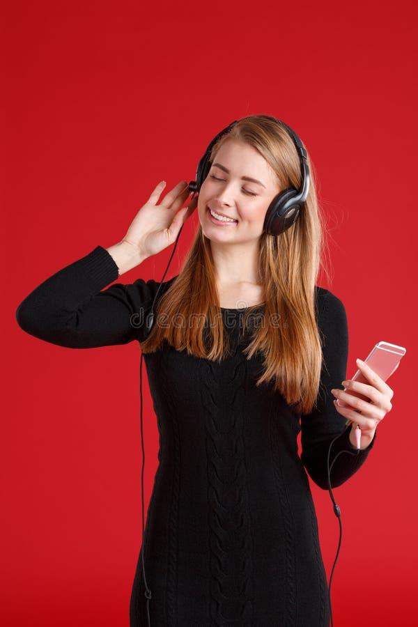 La fille heureuse, avec des yeux a fermé apprécier la musique dans des écouteurs, tenant le smartphone Sur un fond rouge image libre de droits