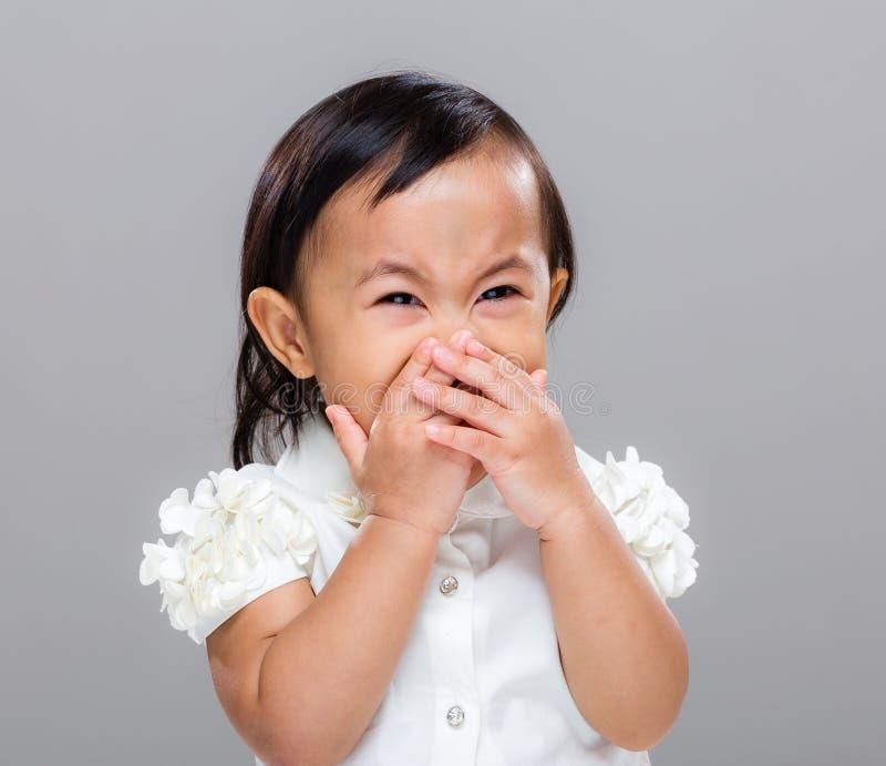La fille heureuse avec la main couvrent sa bouche photos stock