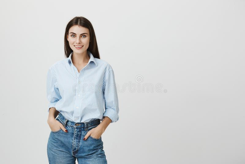 La fille heureuse belle positive avec les cheveux foncés dans la chemise élégante pose contre le mur de studio avec des mains dan images stock