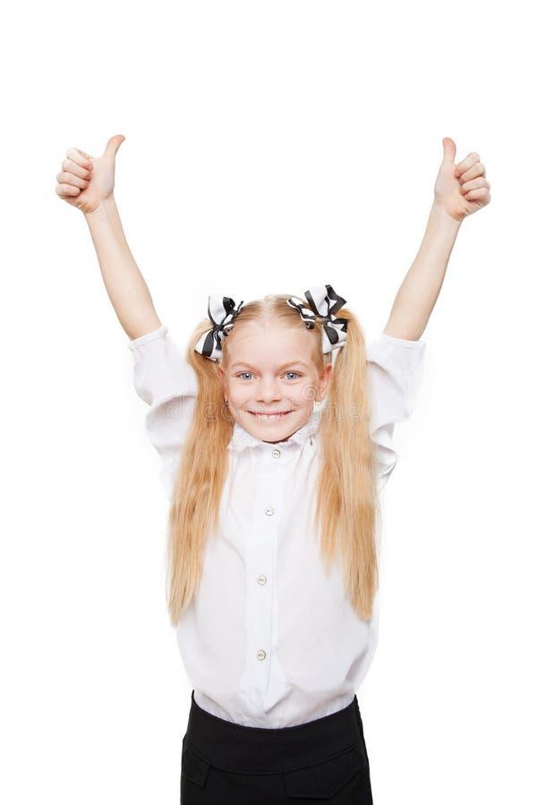 La fille heureuse d'école montrant des pouces lèvent le symbole photos libres de droits