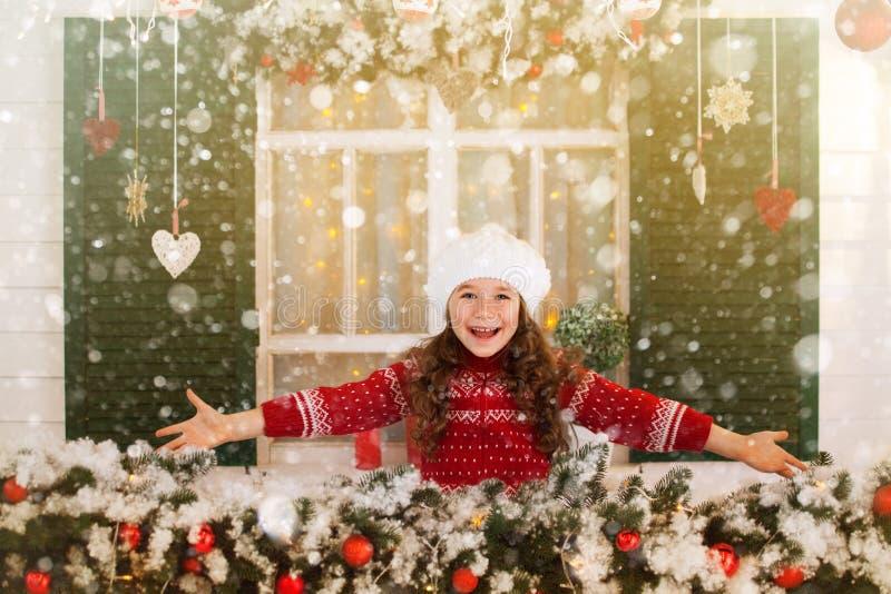 La fille heureuse d'enfant étire sa main pour attraper les flocons de neige en baisse photo stock