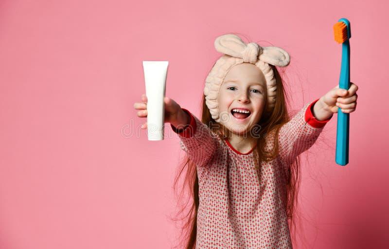 La fille heureuse d'enfant avec la brosse à dents balaye des dents et des sourires photographie stock