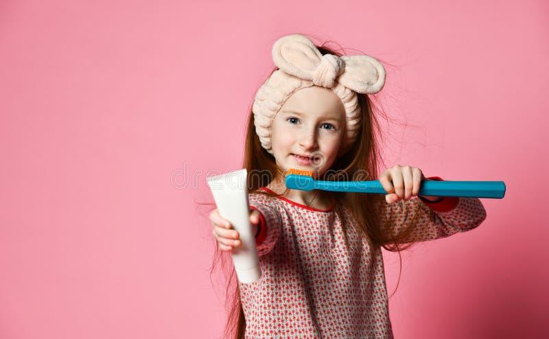 La fille heureuse d'enfant avec la brosse à dents balaye des dents et des sourires images stock