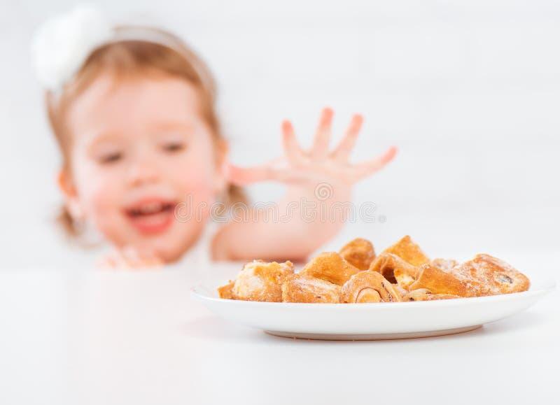 La fille heureuse d'enfant mange des biscuits et du lait images libres de droits