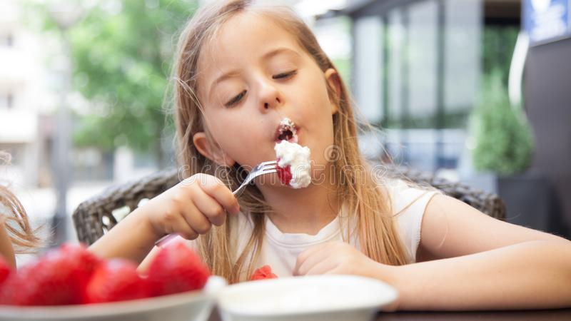 La fille heureuse d'enfant mange des fraises pendant l'été, jeune smil mignon photos libres de droits