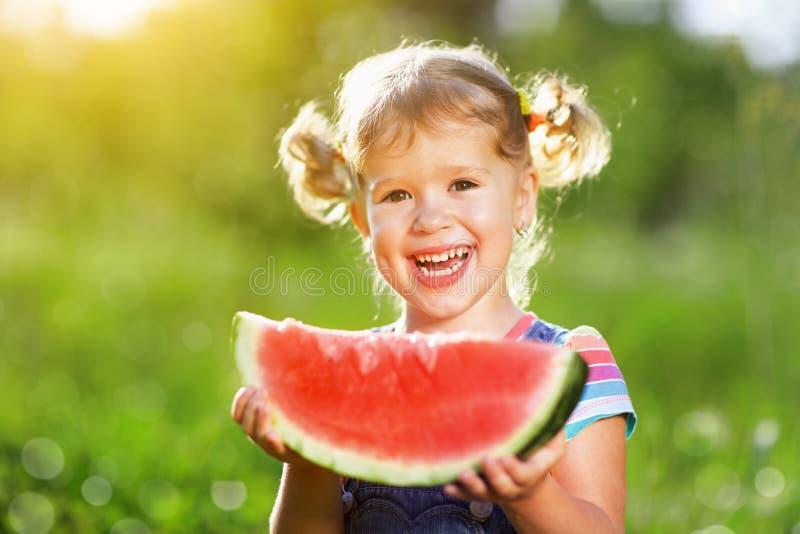 La fille heureuse d'enfant mange la pastèque photographie stock