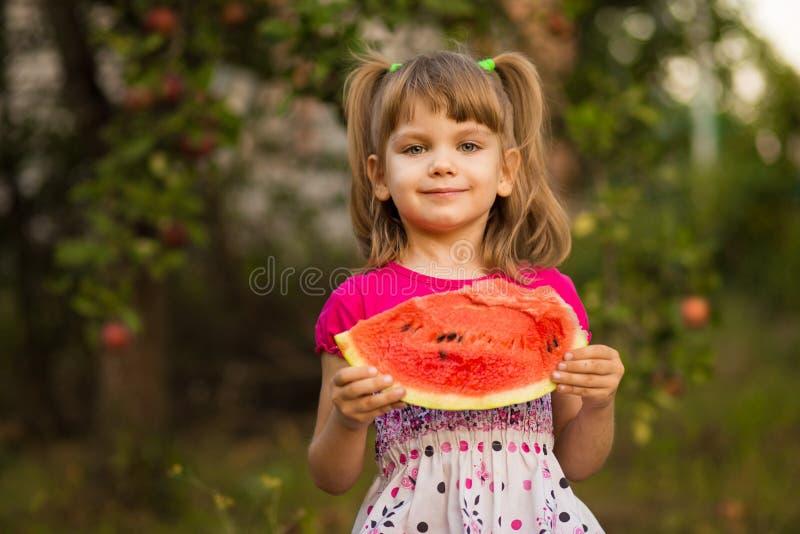 La fille heureuse d'enfant mange la pastèque en été Concept sain photographie stock libre de droits