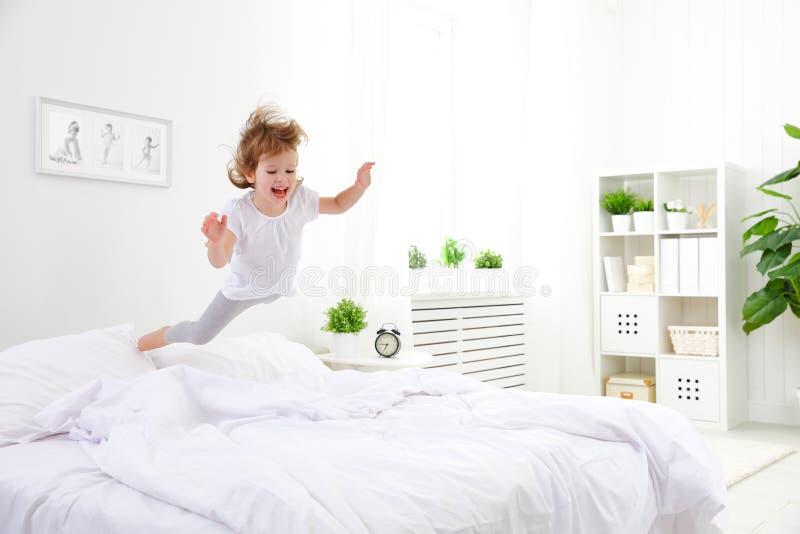 La fille heureuse d'enfant saute et joue le lit photographie stock