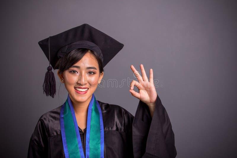 La fille heureuse d'obtention du diplôme fait le symbole d'approbation avec la main images stock