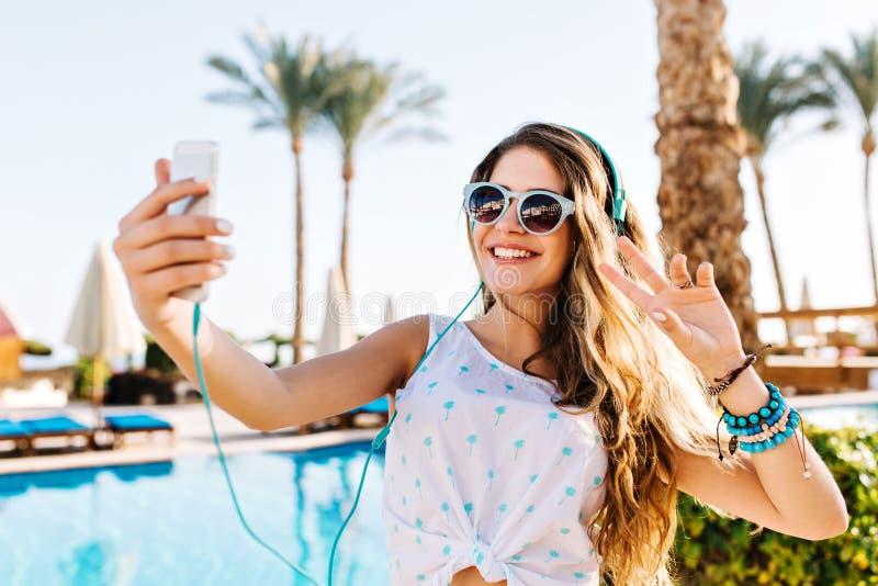 La fille heureuse dans des lunettes de soleil avec la peau bronzée faisant le selfie avec la paix se connectent le fond de palmie photographie stock libre de droits