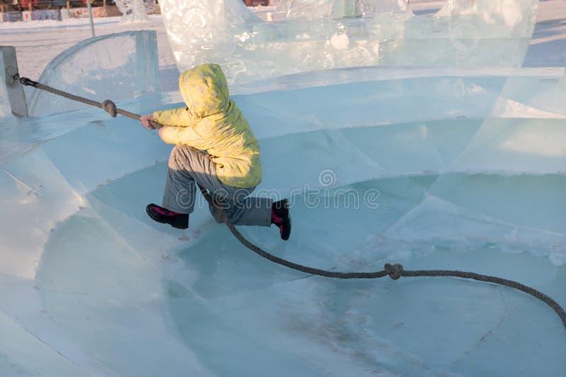 La fille heureuse dans des vêtements chauds jaunes joue dans le grand plat de glace photo libre de droits