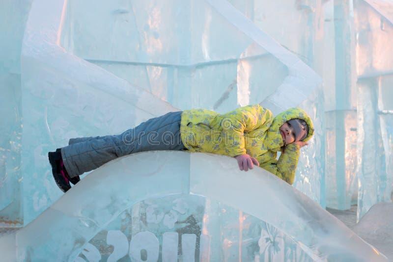 La fille heureuse dans des vêtements chauds jaunes se trouve sur la sculpture en glace photos stock