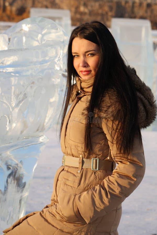 La fille heureuse dans des vêtements chauds se tient près de la grande glace photo stock