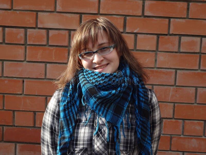La fille heureuse dans les verres et la veste de plaid et l'écharpe restent au sujet de bric photographie stock