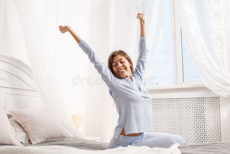 La fille heureuse de brune dans le pyjama bleu-clair étire ses bras vers le haut de se reposer sur le lit d'auvent à côté de la f photo libre de droits