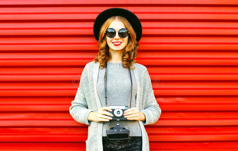 La fille heureuse de joli automne tient le rétro appareil-photo sur le fond rouge photos stock