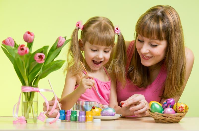La fille heureuse de mère et d'enfant décorent des oeufs de pâques image stock