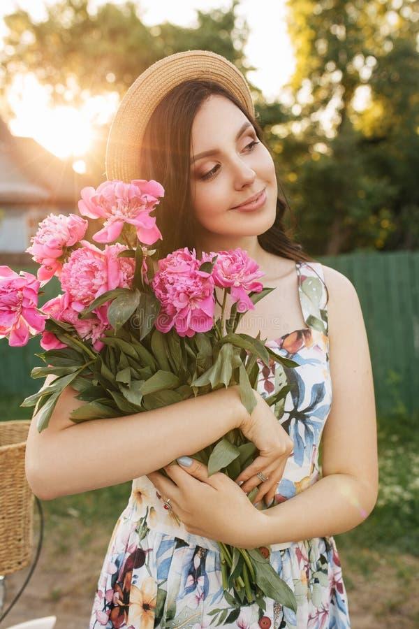 La fille heureuse de sourire de brunnete dans des blanc-fleurs s'habillent et chapeau avec les peones roses Sun est sur le fond images libres de droits