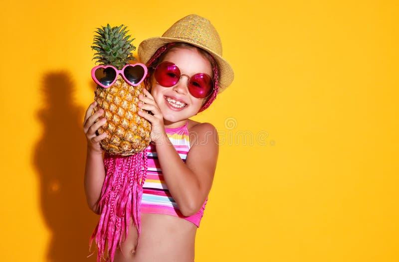 La fille heureuse drôle d'enfant dans le maillot de bain, les verres roses et le chapeau avec l'ananas rit sur le fond jaune photos libres de droits