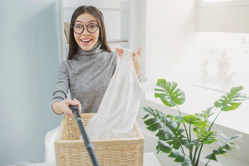 La fille heureuse et gentille tient les vêtements blancs dans sa main et prend des photos de elle C'est un panier pour des vêteme photos libres de droits