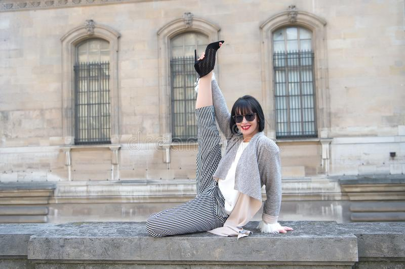 La fille heureuse font l'exercice s'étendant fendu de jambe sur la barrière en pierre photo stock