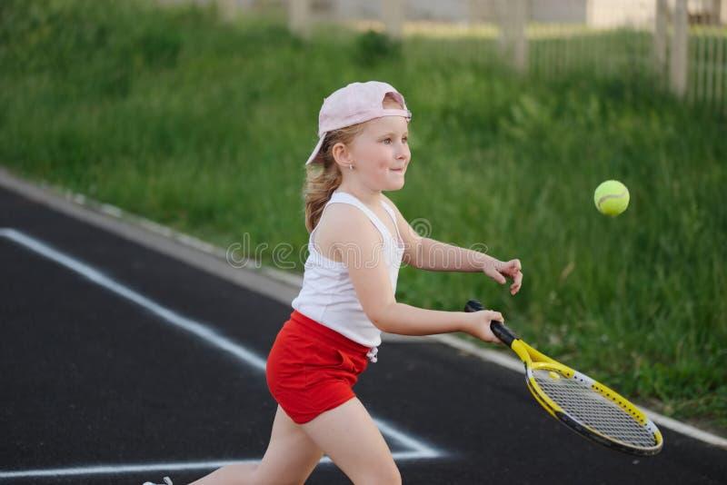 La fille heureuse joue au tennis sur la cour dehors image stock