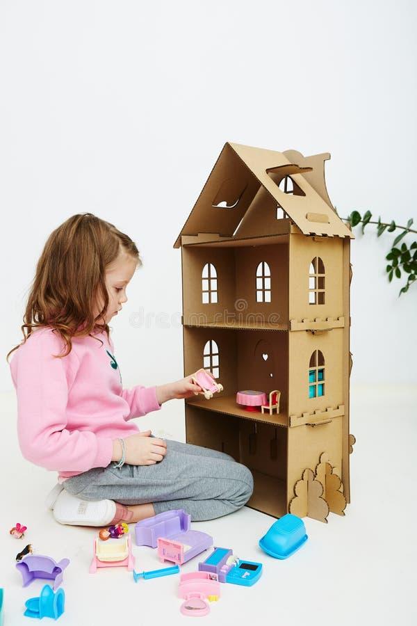 La fille heureuse joue avec des meubles de maison de poupée et de maison de poupée Le bel enfant drôle a l'amusement photographie stock