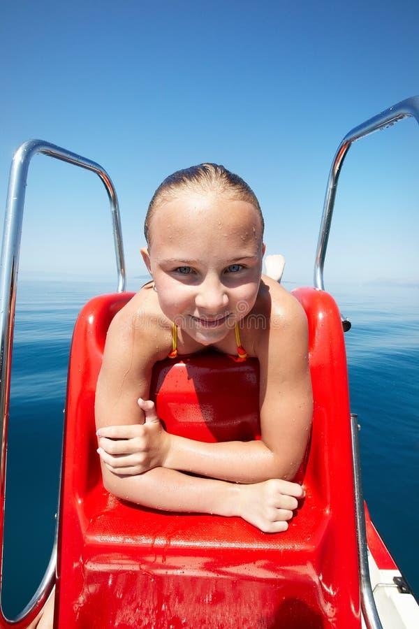 La fille heureuse la prend un bain de soleil sur le bateau de plage photographie stock libre de droits