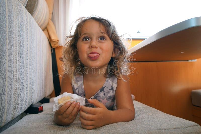 La fille heureuse mange dans le campeur image stock