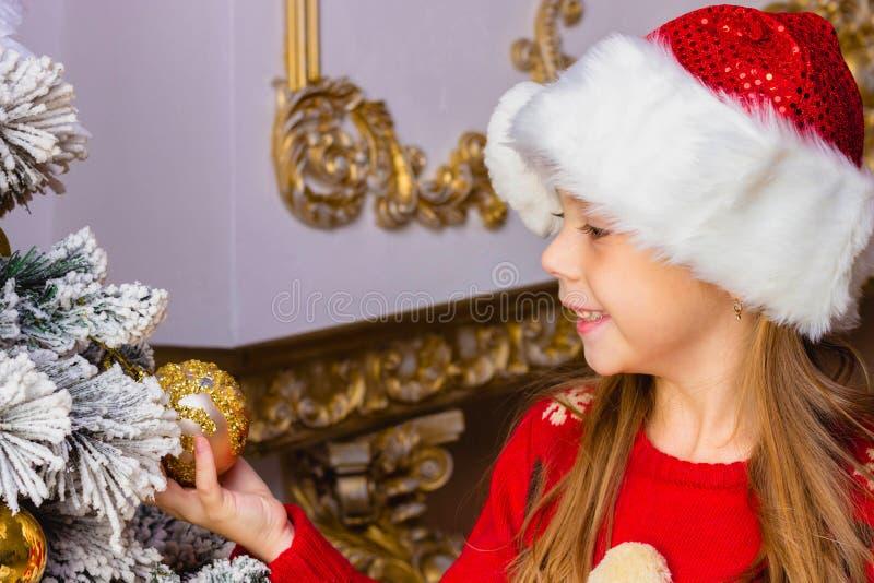 La fille heureuse mignonne dans le chapeau rouge accroche des décorations photo stock