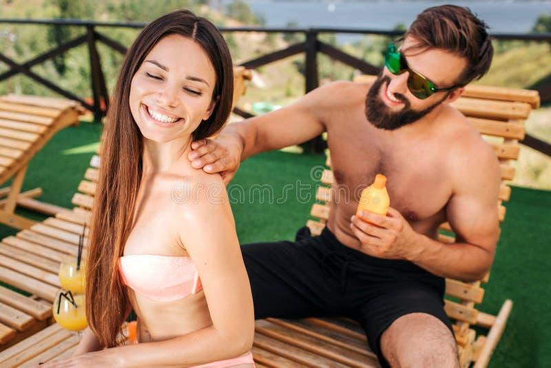 La fille heureuse s'assied et sourit Elle kepps ses yeux fermés Le type met de la crème de sunproof sur ses épaules Il porte photographie stock