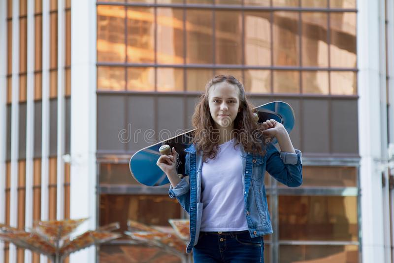 La fille heureuse se tient près d'un bâtiment tenant un panneau de patin dans une ville près d'un édifice haut images stock