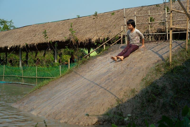 La fille humide brouillée de mouvement apprécie des jeux le glisseur dans l'étang de boue dans la ferme images stock