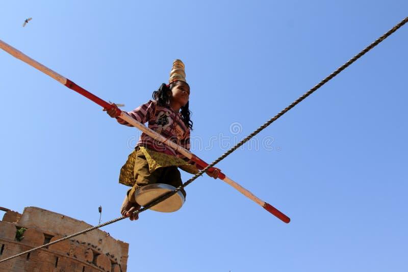 La fille indienne exécute des acrobaties de rue en marchant la corde photos libres de droits