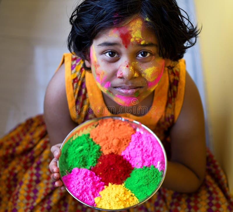 La fille indienne joue avec le plateau complètement de couleurs pour célébrer Holi photo libre de droits