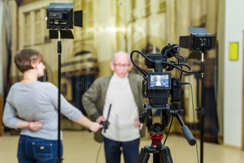 La fille interviewe l'homme Tir visuel dans l'intérieur Affichage d'affichage à cristaux liquides sur le caméscope images stock