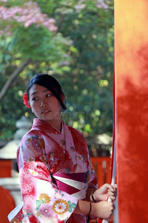 La fille japonaise dans le support de robe de kimono et le tissu de crochet rope à sonner la cloche pour bénissent au tombeau au  images stock