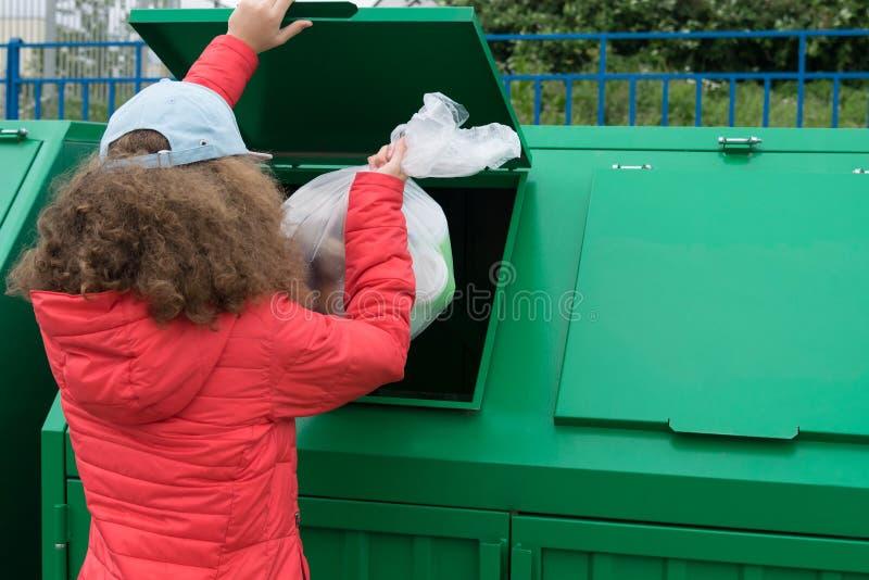 La fille jette le paquet avec des déchets dans le conteneur de déchets verts photo libre de droits