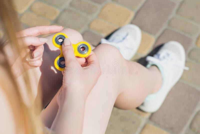 La fille jouant avec le fileur de main tout en se reposant sur de banc gamer de jeu de nouveauté de dépendance dehors un nouveau  image stock