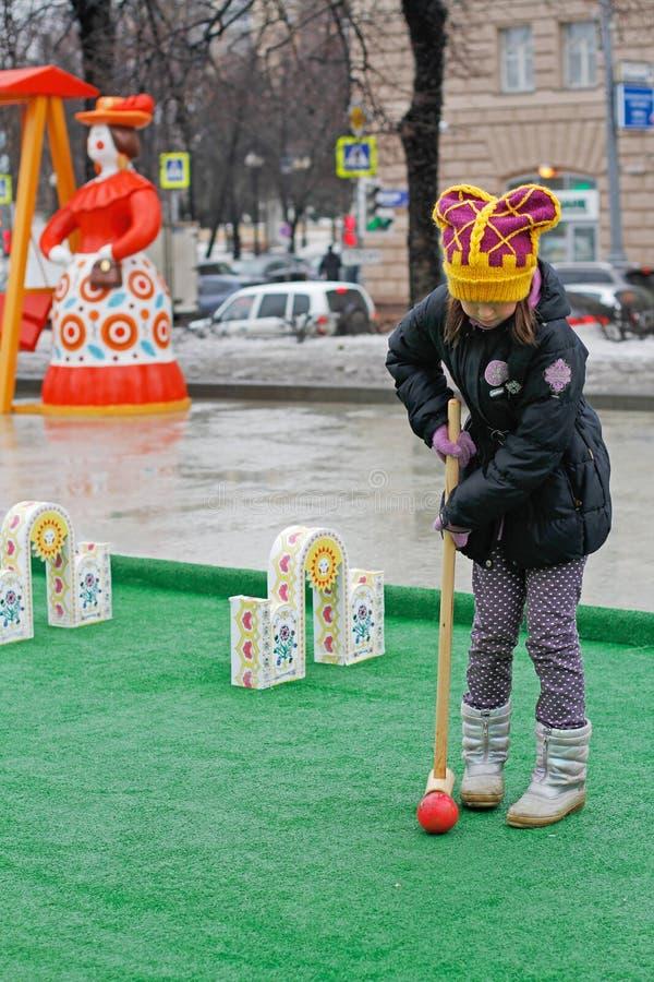 La fille jouant le cricket au ` national russe de festival Shrove le ` sur le boulevard de Tverskoy à Moscou photographie stock