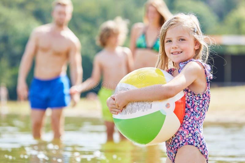 La fille joue avec une boule colorée en mer photo stock