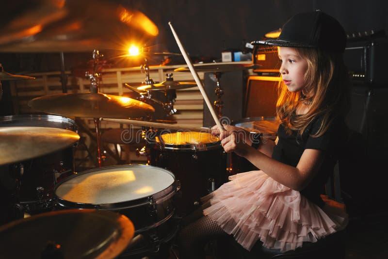La fille joue des tambours dans le studio d'enregistrement photographie stock