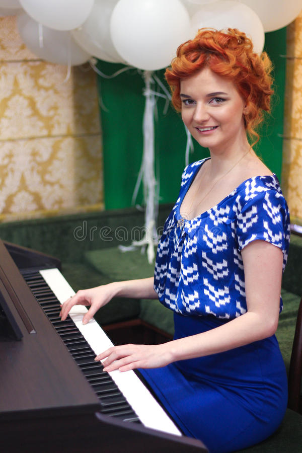 La fille joue l'instrument de musique de clavier image libre de droits